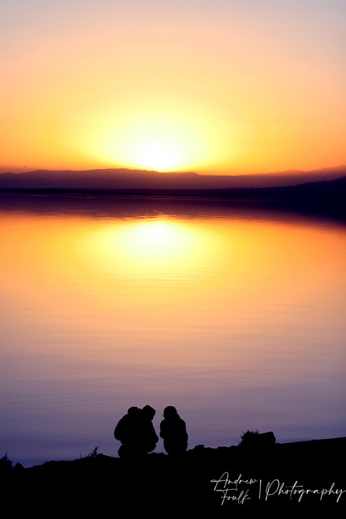 Two young lovers sit on the shore of the Salton Sea and enjoy one of the areas signature sunsets.