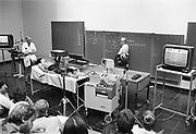 Nederland, Nijmegen, 15-10-1983College Fysiologie aan de Katholieke universiteit , KUN, later RU, Radboud Universiteit. Studenten en hoogleraar in collegezaal met voor die tijd moderne apparatuur om de les te ondersteunen. Video en beeldscherm. Een student ligt als proefpersoon op een onderzoekbed en is aangesloten met elektroden op meetapparatuur. het college gaat over de werking van het hart.FOTO: FLIP FRANSSEN/ HOLLANDSE HOOGTE