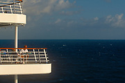 Passengers enjoy the sea view from their vacation ship's deck on 15th May 1996, aboard the Carnival cruise ship Ecstasy, off the Gulf of Mexico, USA.