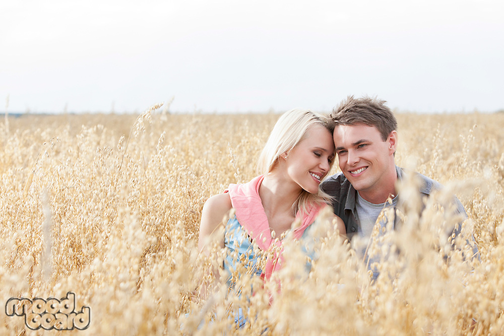 Happy loving young couple sitting amidst field