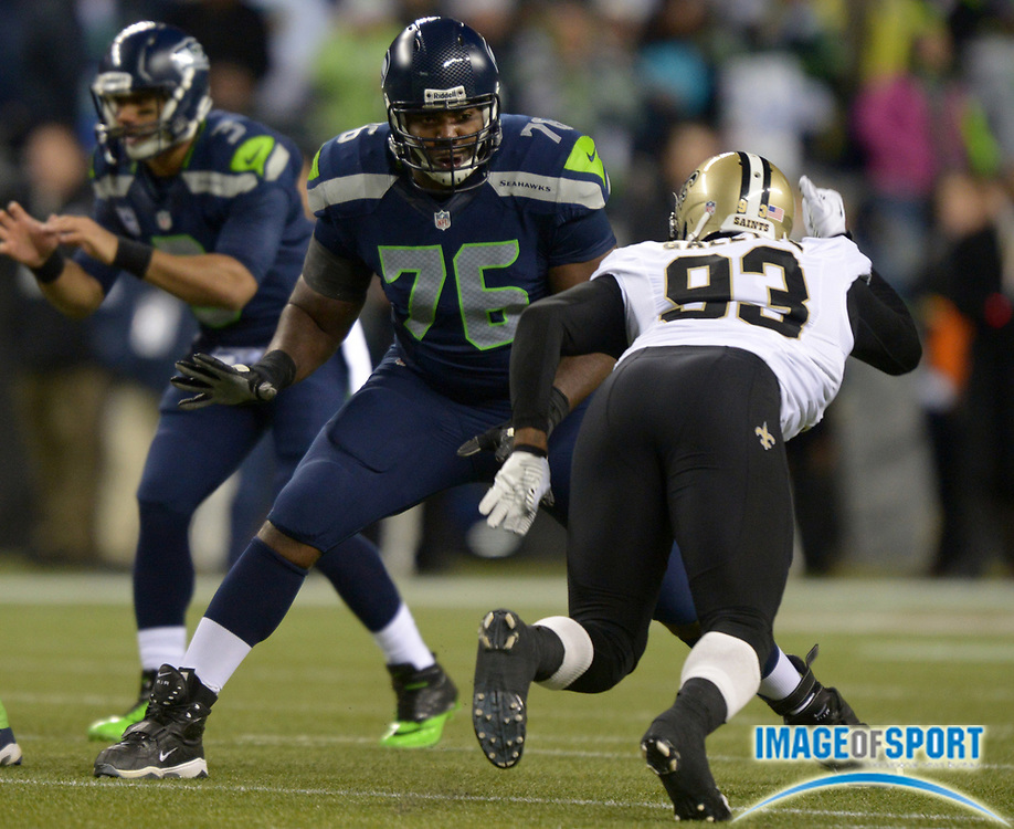 Dec 2, 2013; Seattle, WA, USA; Seattle Seahawks tackle Russell Okung (76) defends against New Orleans Saints linebacker Junior Galette (93) at CenturyLink Field. The Seahawks defeated the Saints 34-7.