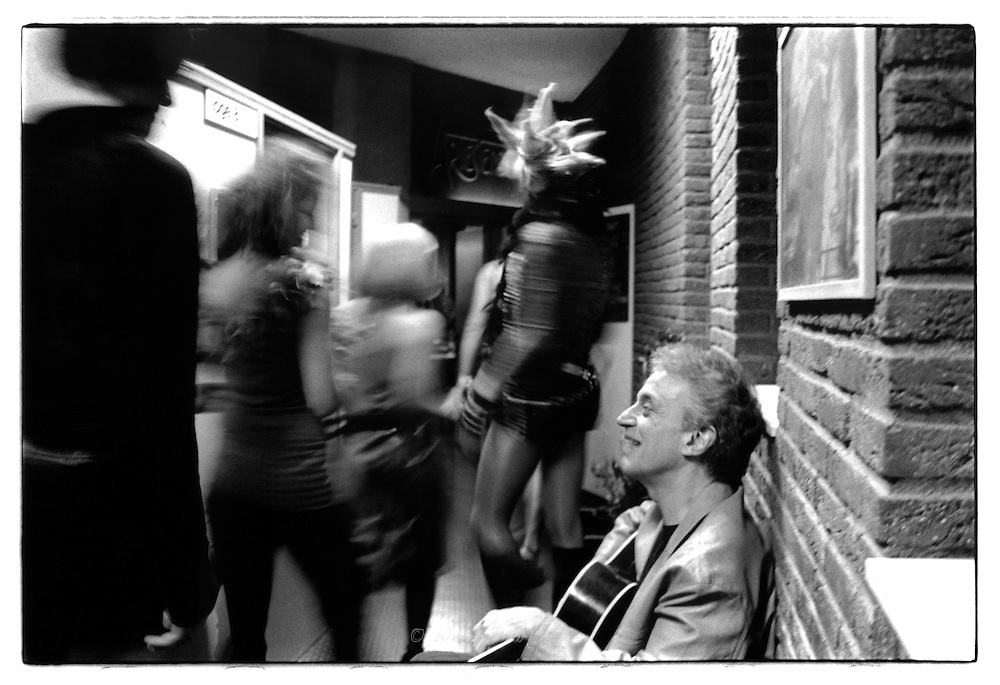 Singer/songwriter Doug Mac Leod surprised while a group of transvestites pass through the hall. Backstage at C.C. de Warande, Turnhout, Belgium, 2002