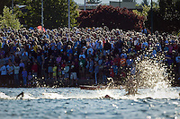 Hundreds of spectators watch as the professional Ironman competitors make their way toward the beach as the athletes finish their first lap of the swim portion.