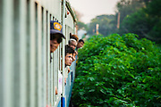 07 JANUARY 2013 - KANCHANABURI, THAILAND:  Passengers look out the window of a third class train car on the train between Bangkok (Thonburi station) and Kanchanaburi. Thailand has a very advanced rail system and trains reach all parts of the country.    PHOTO BY JACK KURTZ