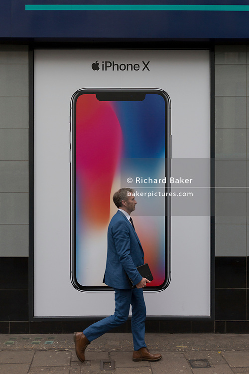A man walks past an ad for the new Apple iPhone X outside a branch of Carphone Warehouse, on 22nd November 2017, in London England.