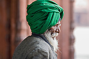 INDIA, OLD DELHI:  Elderly East Indian man wearing a green turban as he walks through the courtyard of the Jama Masjid Mosque at prayer time in Old Delhi.