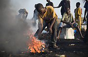 A boy sits on the back casing of a computer monitor while his friend stirs the fire to recover copper from electrical cables near the Agbogboloshie market in Accra, Ghana on Thursday August 21, 2008.