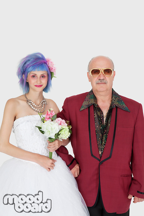 Portrait of beautiful young bride standing arm in arm with father
