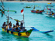 03 AUGUST 2017 - KUTA, BALI, INDONESIA: An outrigger brings a crew of fishermen who work on a trawler into shore on Jimbrana Beach in Kuta. The beach is close to the airport and a short drive from other beaches in southeast Bali. Jimbrana was originally a fishing village with a busy local market. About 25 years ago, developers started building restaurants and hotels along the beach and land prices are rising. The new emphasis on tourism is changing the nature of the area but the fishermen are still busy very early in the morning.     PHOTO BY JACK KURTZ