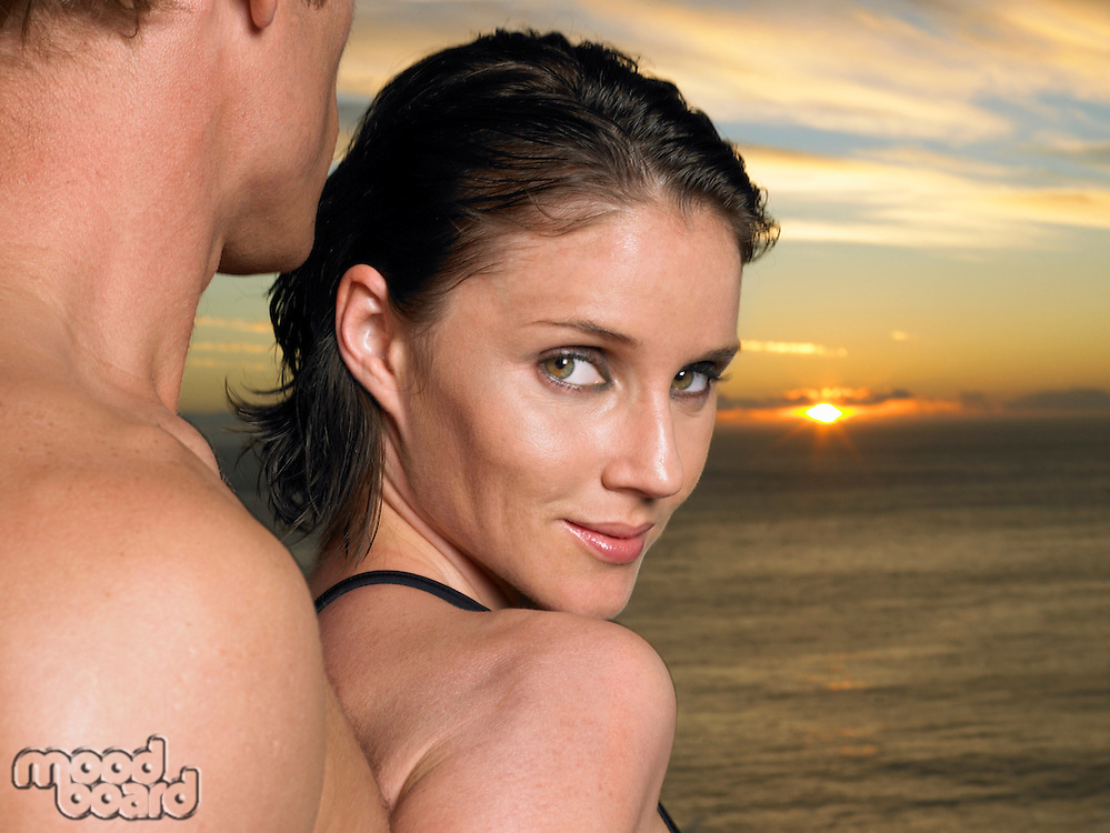 Woman looking over shoulder with man behind her at sunset over ocean