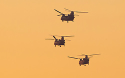 © Licensed to London News Pictures. 04/12/2019. Watford, UK. Three US Army Chinook helicopters circle over The Grove Hotel as they wait for US President Donald Trump to leave the NATO Summit after cancelling his press conference.  World leaders have finished attending a series of events over the two day NATO summit which marked the 70th anniversary of the alliance of nations. Photo credit: Peter Macdiarmid/LNP