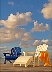 adirondack deck chairs on dock in Florida with puffy clouds on summer day