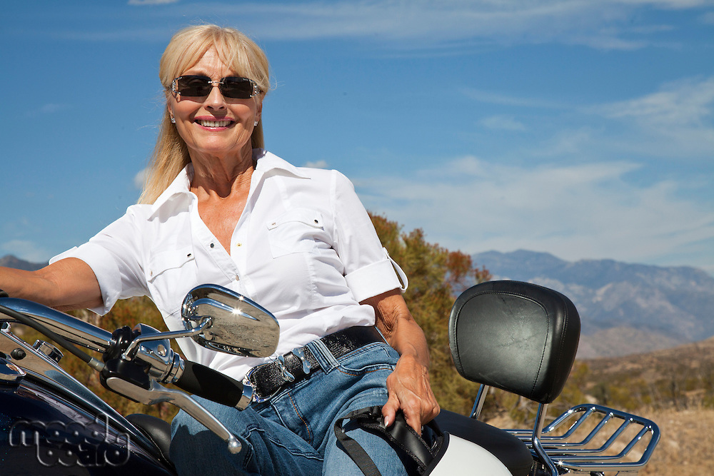 Senior woman sitting on motorcycle on desert road
