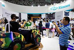 Men at virtual reality simulator exhibit at Shenzhen Hi Tech Fair 2016.