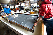 Artisans make washi paper at Iwano Heizaburo Seijijo in Echizen, Fukui Prefecture, Japan on 21 Feb. 2013. Photographer: Robert Gilhooly  .Artisans tilt a frame to create an even sheet of washi paper at Iwano Heizaburo Seijijo in Echizen, Fukui Prefecture, Japan on 21 Feb. 2013. Photographer: Robert Gilhooly    .