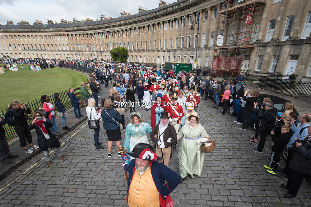 Bath, Somerset, UK. 9th September 2017. Pictured: The Promenade begins as participants saunter through the Royal Crescent. /  Around 600 people dressed in period attire take part in the Grand Regency Costumed Promenade in Bath marking the 200th anniversary of the English novelist Jane Austen's death. The Promenade commenced mid-morning from the world famous Royal Crescent Lawn and made its way through the historic Georgian streets and main shopping area of the city before finishing at Parade Gardens. In 2014 the Jane Austen Festival achieved the Guinness World Record TM for 'The largest gathering of people dressed in Regency costumes'. The Somerset city is currently host to the 17th annual Jane Austen Festival with an expected 4000 visitors taking part in events such as film screenings, book readings, workshops, dances, balls, talks, concerts and theatricals. // Lee Thomas, Tel. 07784142973. Email: leepthomas@gmail.com  www.leept.co.uk (0000635435)