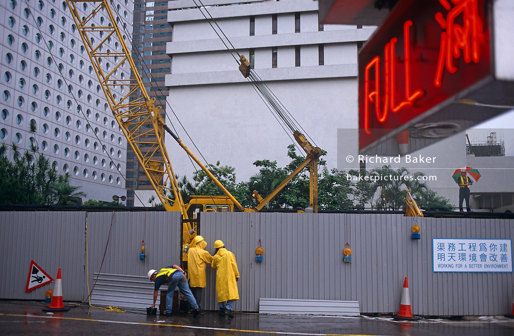 Construction workers in Central Hong Kong carry on working during a monsoonal rain shower on the last day of British rule.