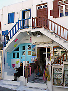 2 shops, old woman sit on steps, white buildings, bright trim, Cycladic architecture