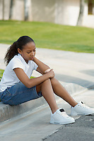Girl (7-9) sitting on curb