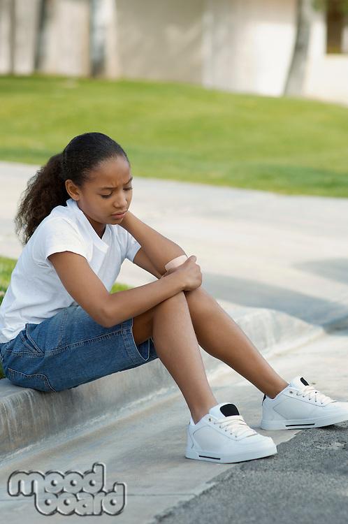 Girl (7-9) sitting on curb