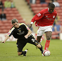 Photo: Aidan Ellis.<br /> Barnsley v Cardiff City. Coca Cola Championship. 29/09/2007.<br /> Cardiff's Kevin McNaughton is tumbled to the ground by Barnsley's Kayode Odejayi