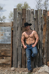 shirtless muscular cowboy leaning against a wooden fence