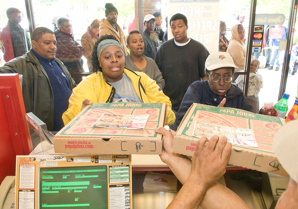Papa John's employee Marcus Jackson of Baltimore, MA hands out two more pepperoni pizzas to customers at the Shaker Heights store on Chagrin Road on Thursday, May 8, 2008. The popular pizza chain sold 23 cent pizzas on Thursday in order to win back the loyalty of Cleveland area customers after a marketing blunder involving LeBron James that offended Cleveland Sports fans.