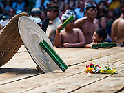 22 JULY 2016 - TENGANAN DUAH TUKAD, BALI, INDONESIA: The stage with rattan shields, pandanus leaves and Hindu offerings before the pandanus fights in the Tenganan Duah Tukad village on Bali. The ritual Pandanus fights are dedicated to Hindu Lord Indra. Men engage in ritual combat with spiky pandanus leaves and rattan shields. They usually end up leaving bloody scratches on the combatants' backs. The young girls from the community wear their best outfits to watch the fights. The fights have been traced to traditional Balinese beliefs from the 14th century CE. The fights are annual events in the Balinese year, which is 210 days long, or about every seven months in the Gregorian calendar.    PHOTO BY JACK KURTZ