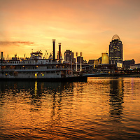 Photo of Cincinnati skyline and riverboat at sunset at night along the Ohio River including Great American Insurance building, Great American Ball Park, US Bank Arena, Scripps building, and PNC Tower building. Photo is high resolution and was taken in 2012.