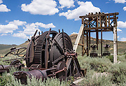 "Mine headframe and winch at Bodie, California's official state gold rush ghost town. A headframe (also called a gallows frame, winding tower, hoist frame, pit frame, shafthead frame, headgear, headstock or poppethead) is the structural frame above an underground mine shaft. Bodie State Historic Park lies in the Bodie Hills east of the Sierra Nevada mountain range in Mono County, near Bridgeport, California, USA. After W. S. Bodey's original gold discovery in 1859, profitable gold ore discoveries in 1876 and 1878 transformed ""Bodie"" from an isolated mining camp to a Wild West boomtown. By 1879, Bodie had a population of 5000-7000 people with 2000 buildings. At its peak, 65 saloons lined Main Street, which was a mile long. Bodie declined rapidly 1912-1917 and the last mine closed in 1942. Bodie became a National Historic Landmark in 1961 and Bodie State Historic Park in 1962."