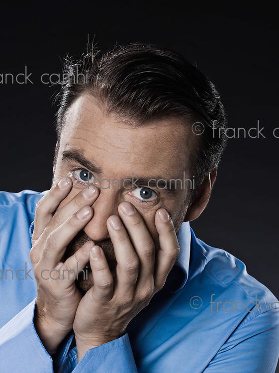 caucasian man unshaven fear hiding portrait isolated studio on black background