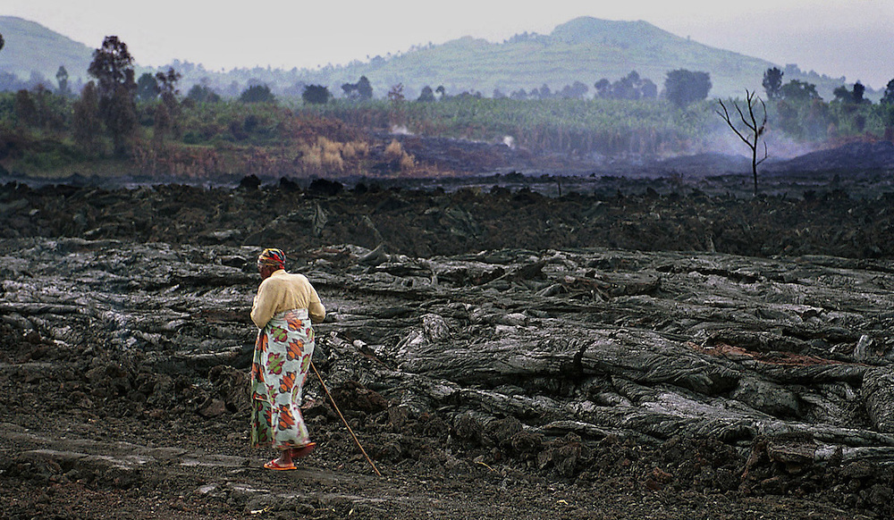 A woman walks home from the centre of a destroyed Goma, Democratic Republic of Congo.  Goma, a city of 400,000 people was engulfed in lava from the Nyiragongo volcano which erupted on 17/1/2002 .
