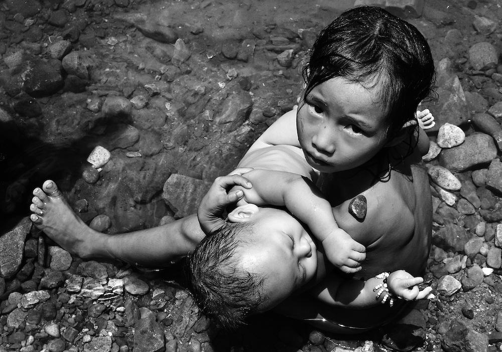 Hmong children enjoying a stream in Bokeo, Laos.