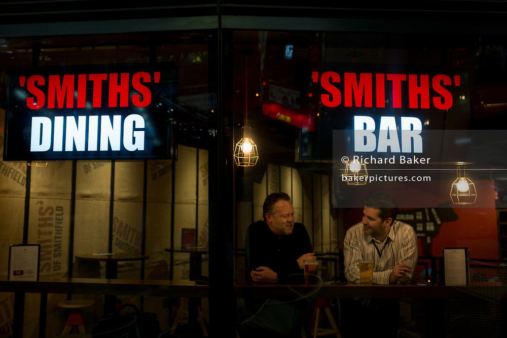 Two men drink and talk in the window of Smiths Bar on Cannon Street in the heart of the Square Mile, the capital's historical and financial centre, on 1st November 2017, in the City of London, England.