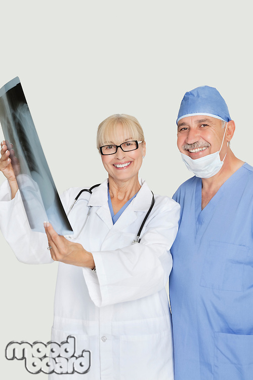 Portrait of happy senior male surgeon and female doctor with x-ray over gray background