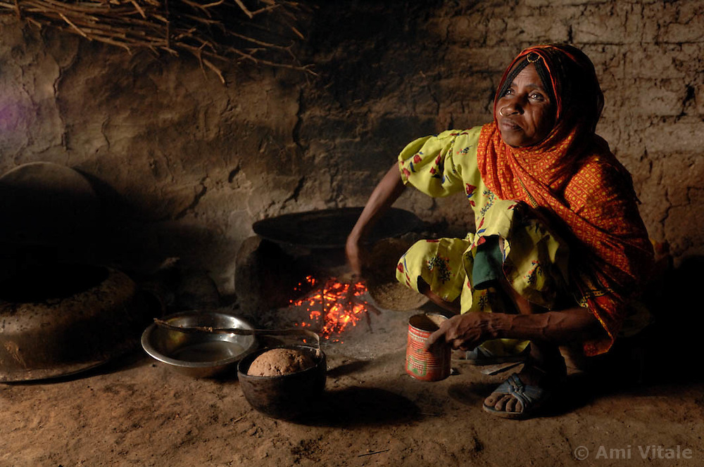 """Kadija makes a traditional bread  called injero, inside her home  in Barentu, Eritrea August 25, 2006. Kadija is a traditional birth assistant as well as a recipient of a donkey from the women's union """"Hamade"""". (Ami Vitale)"""