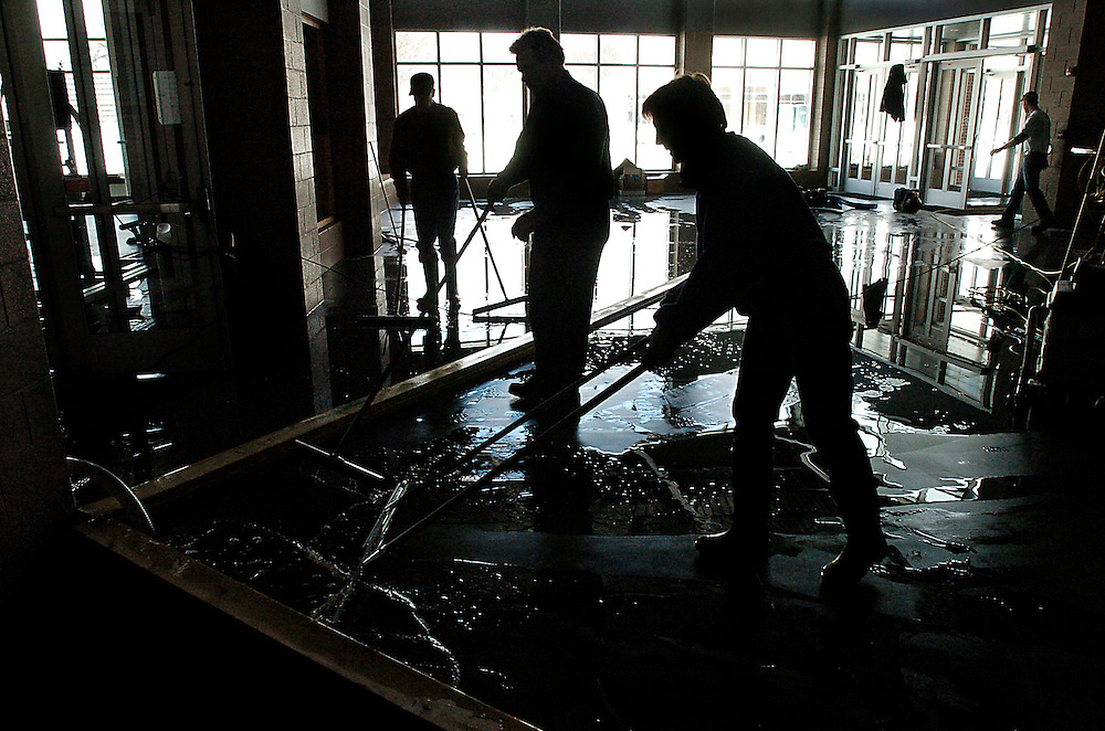 Dan Hannaher, from left, Denny Stinar and Barb Lewis work to funnel floodwater out of the Ellig Center at the flooded Oak Grove Lutheran School in Fargo, N.D. The River briefly breached the dike early in the morning pouring water into the school campus. Crews managed to largely contain the flooding to the school campus preventing more widespread damage in nearby areas.