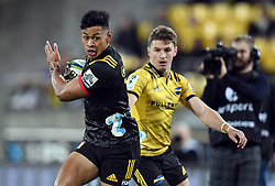 Chiefs Solomon Alaimalo, left, slips inside Hurricanes Beauden Barrett in the Super Rugby match at Westpac Stadium, Napier, New Zealand, Friday, April 13, 2018. Credit:SNPA / Ross Setford