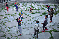 Boys playing volleyball a the center of the village, while an elderly womandoes her chores.