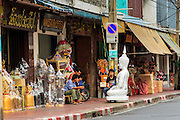 "12 NOVEMBER 2012 - BANGKOK, THAILAND:   Men set on Bamrung Muang Street in Bangkok. Thanon Bamrung Muang (Thanon is Thai for Road or Street) is Bangkok's ""Street of Many Buddhas."" Like many ancient cities, Bangkok was once a city of artisan's neighborhoods and Bamrung Muang Road, near Bangkok's present day city hall, was once the street where all the country's Buddha statues were made. Now they made in factories on the edge of Bangkok, but Bamrung Muang Road is still where the statues are sold. Once an elephant trail, it was one of the first streets paved in Bangkok. It is the largest center of Buddhist supplies in Thailand. Not just statues but also monk's robes, candles, alms bowls, and pre-configured alms baskets are for sale along both sides of the street.    PHOTO BY JACK KURTZ"