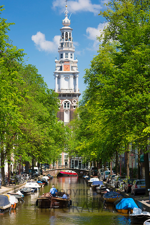 View of Zuiderkerk in Old Town and tourist boat taking tour group along Dutch canals, Groenburgwal in Amsterdam, Holland