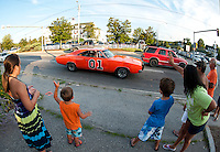 "Olivia Aubin, Zachary Haslam, Jacob Aubin and Renee Haslam wave as the ""General Lee"" a 1969 Dodge Charger driven by David Fazio goes through downtown Meredith Saturday evening for the Cruise Night Parade.  (Karen Bobotas/for the Laconia Daily Sun)"