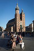 Visitors rest on seating opposite the Church of St Mary on Rynek Glowny market square, on 22nd September 2019, in Krakow, Malopolska, Poland.