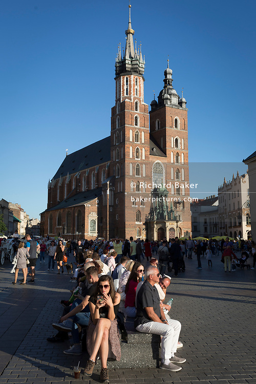 Visitors rest on seating opposite the Church of St Mary on Rynek Glowny market square, on 22nd September 2019, in Krakow, Malopolska, Poland.