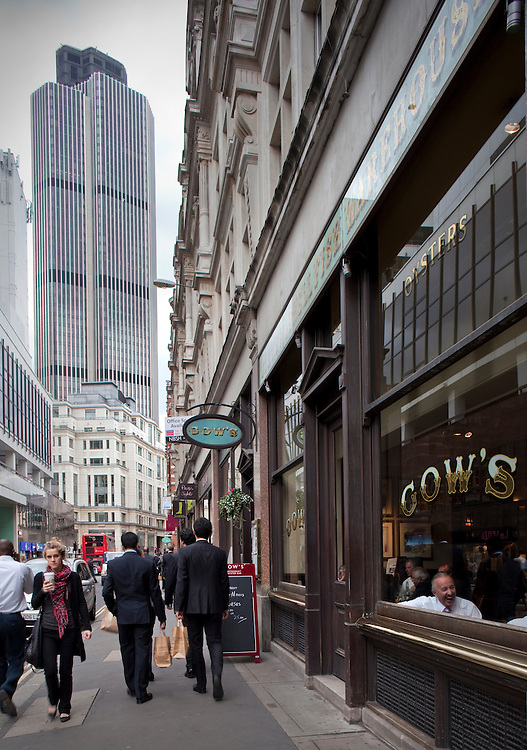 street in city of london at lunchtime with office workers on pavement and tower 42 in distance.