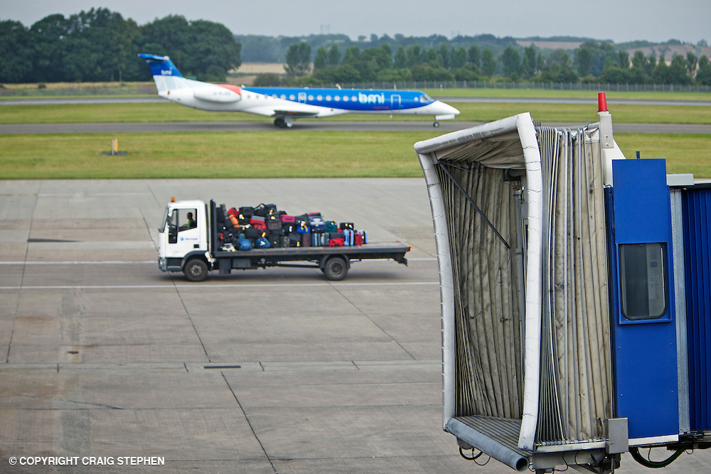 Airside at airport showing jet taxiing, luggage on truck and passenger ramp