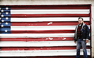 man with american flag painted on garage door.  albuquerque, new mexico.