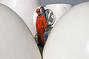 Gansu, China - 25 Feb 2010. A worker stands between wind turbine rotoors at Gansu Jinfeng Wind Power Equipment Co. Ltd. in Jiuquan, Gansu Province, China. China has set a target for renewable energy consumption of 40 percent of the market by the year 2050. Photographer: Markel Rendondo/Greenpeace.