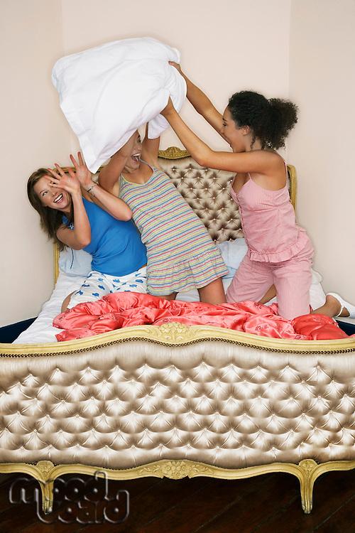 Teenage Girls pillow fighting kneeling on funky bed