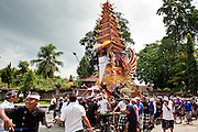 Apr. 25 -- UBUD, BALI, INDONESIA:   The funeral tower for Cokorde Gede Raka, a member of Ubud's royal family, is brought into the cremation site, Sunday, Apr. 25. Balinese are Hindus and cremate their dead. Balinese funerals are elaborate - and expensive - affairs. A funeral for one person costs a minimum of 45 million rupiah (about $5,000 US). The body is placed into the bull's body at the cremation and cremated in the bull. The funeral pyre is burnt adjacent to the bull. That is what a family may earn in two to three years. The result is that only the rich can afford formal cremations. The body (in the casket) is placed in the top of the funeral pyre and the procession takes the body to the cremation site. The funeral pyre, and the body, are spun at intersections to confuse the spirits so the soul doesn't try to return to its home and to confuse evil spirits.    PHOTO BY JACK KURTZ